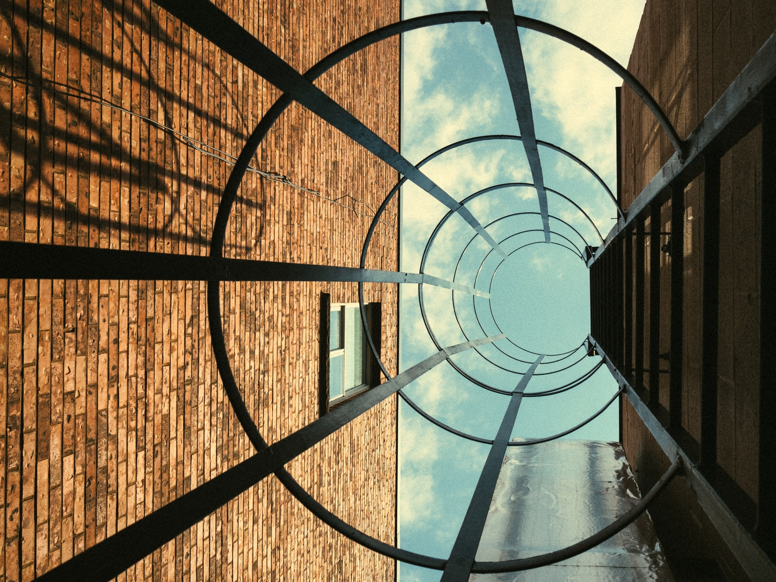worm's eyeview photo of round metal building ladder